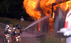 Two firefighters putting out fire